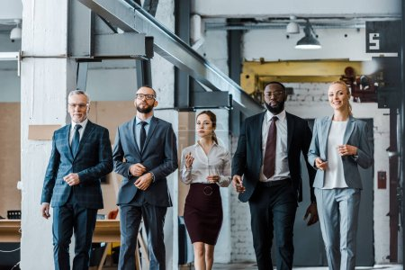 multicultural group of handsome businessmen and attractive businesswomen walking in office