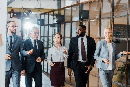 Photo for Multicultural group of handsome businessmen and happy businesswomen walking in office - Royalty Free Image