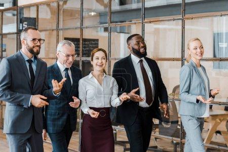 Foto de Grupo multicultural de hombres de negocios alegres y mujeres de negocios felices caminando en la oficina - Imagen libre de derechos