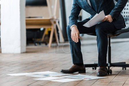 Foto de Cropped view of businessman sitting on chair near charts and graphs on floor - Imagen libre de derechos