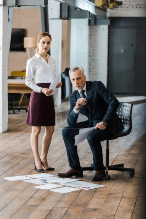 handsome man sitting on chair near businesswoman and charts and graphs on floor