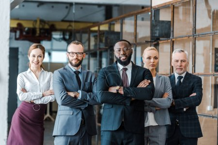 Foto de Successful multicultural businessmen and cheerful businesswomen standing with crossed arms and looking at camera - Imagen libre de derechos