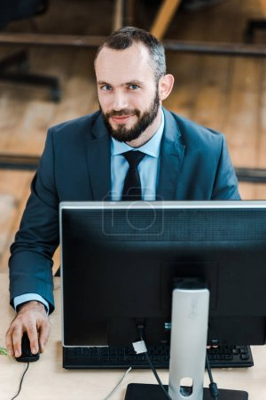 Photo for Cheerful bearded businessman looking at camera near computer monitor in office - Royalty Free Image