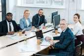 cheerful multicultural businessmen and businesswomen looking at camera in office