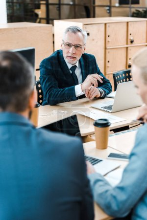 Photo pour Selective focus of bearded businessman in glasses looking at coworkers in office - image libre de droit