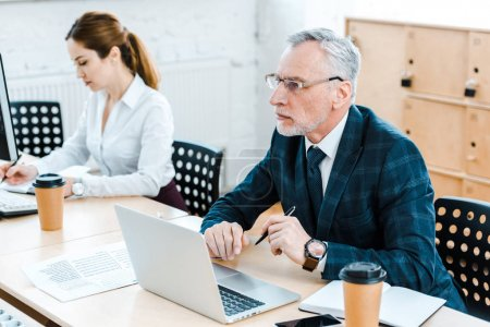 Foto de Selective focus of bearded businessman in glasses using laptop near businesswoman in office - Imagen libre de derechos