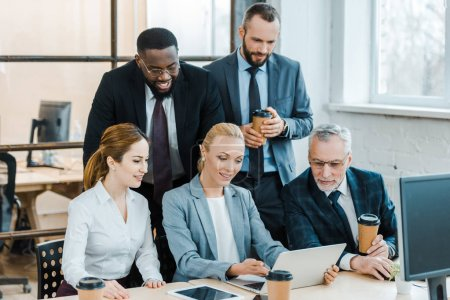 cheerful multicultural businessmen and businesswomen looking at laptop