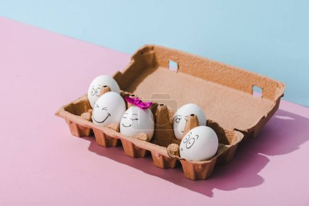 Photo for Eggs with various face expressions in egg carton on blue and pink - Royalty Free Image
