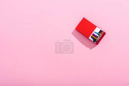 Photo pour Vue du dessus des crayons colorés dans le paquet de cigarettes sur rose avec espace de copie, concept fumeur - image libre de droit