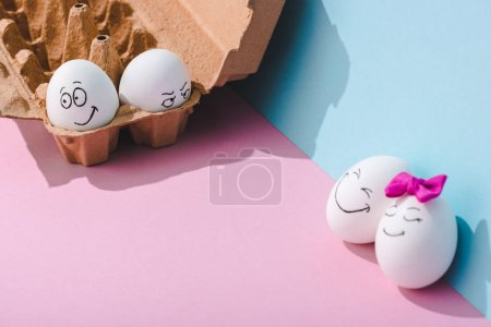 Photo for Eggs with smiling and angry face expressions on blue and pink with copy space - Royalty Free Image