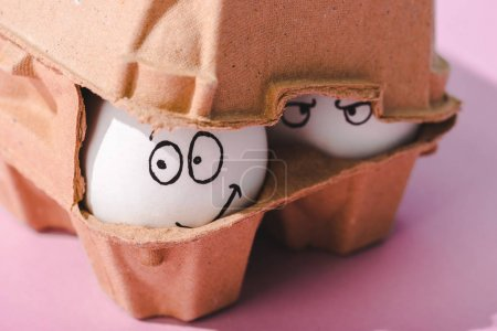 close up of eggs with angry and smiling face expressions in egg carton
