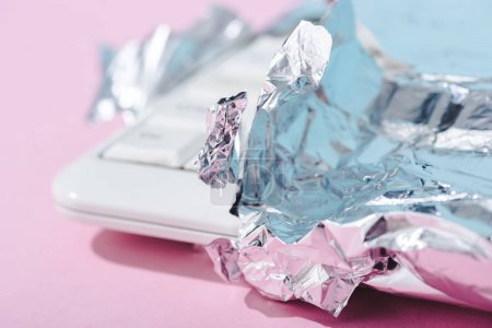 Photo for Selective focus of computer keyboard wrapped in silver foil on pink, Chocolate Bar concept - Royalty Free Image