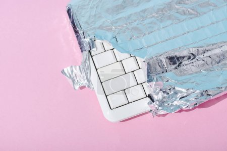 Photo for Top view of computer keyboard wrapped in silver foil on pink, Chocolate Bar concept - Royalty Free Image