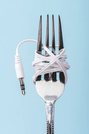 Photo for Close up view of earphones wrapped over metal fork isolated on blue, music concept - Royalty Free Image