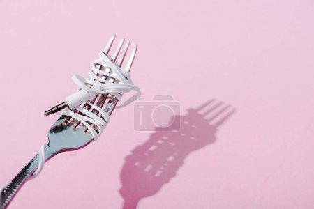 Photo pour Écouteurs enveloppés sur fourche métallique sur rose avec espace de copie, concept de musique - image libre de droit