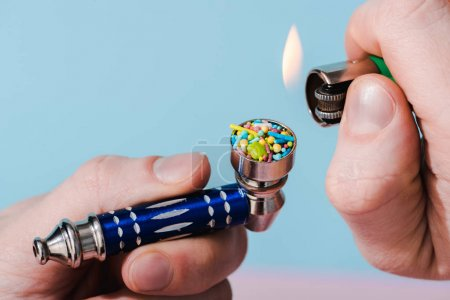 Foto de Vista recortada de la iluminación del hombre Fumar Tubería con coloridos espolvoreos en azul, concepto de adicción al azúcar - Imagen libre de derechos