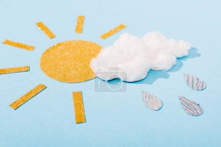 Photo pour Papier pailleté soleil et barbe à papa nuage avec des gouttes de pluie argentées sur bleu - image libre de droit