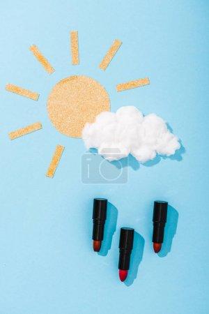 Photo pour Vue supérieure du soleil de papier, du nuage de barbe à papa et des gouttes de pluie de rouge à lèvres sur le bleu - image libre de droit