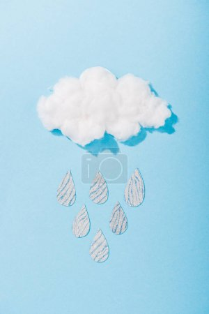 Photo for Top view of cotton candy cloud with glitter raindrops on blue - Royalty Free Image