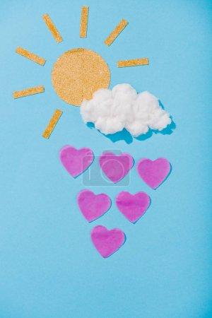 Photo pour Vue du haut du soleil de papier, nuage de barbe à papa et gouttes de pluie en forme de coeur sur le bleu - image libre de droit