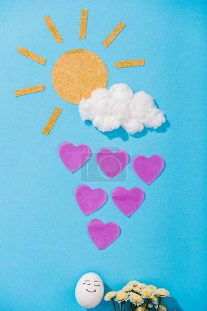 Photo pour Vue supérieure du soleil de papier, nuage de barbe à papa, oeuf avec l'expression heureuse de visage, fleurs et gouttes de pluie en forme de coeur sur le bleu - image libre de droit