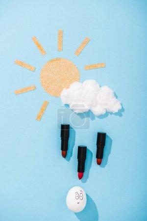 Photo pour Vue supérieure du soleil de papier, nuage de barbe à papa, oeuf avec l'expression étonnée de visage et gouttes de pluie de rouge à lèvres sur le bleu - image libre de droit