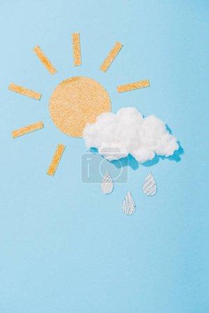 Photo pour Soleil de papier et nuage de barbe à papa avec des gouttes de pluie scintillantes sur le bleu - image libre de droit