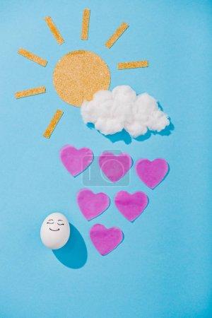 Photo pour Vue supérieure du soleil de papier, nuage de barbe à papa, oeuf avec l'expression heureuse de visage et gouttes de pluie en forme de coeur sur le bleu - image libre de droit