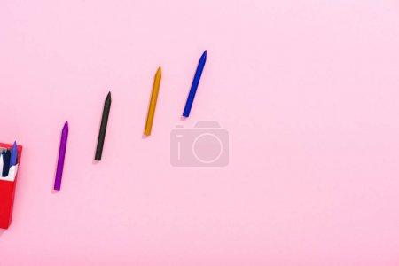Photo pour Vue du dessus de crayons colorés en rangée et paquet de cigarettes sur rose avec espace de copie, concept fumeur - image libre de droit