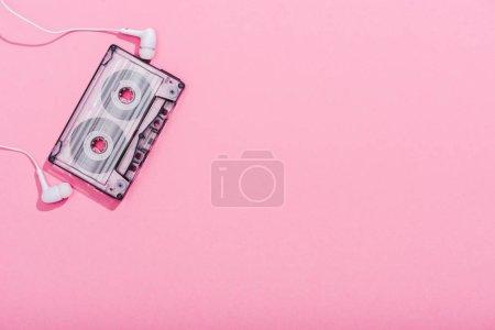 Photo pour Vue du haut de la cassette audio vintage avec écouteurs sur rose avec espace de copie - image libre de droit