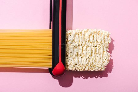 Photo pour Vue de dessus de fer plat, spaghettis et nouilles instantanées ondulées sur rose, concept de lissage des cheveux - image libre de droit