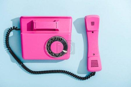 Photo pour Vue supérieure du téléphone de cadran de cru pourpre sur le bleu - image libre de droit