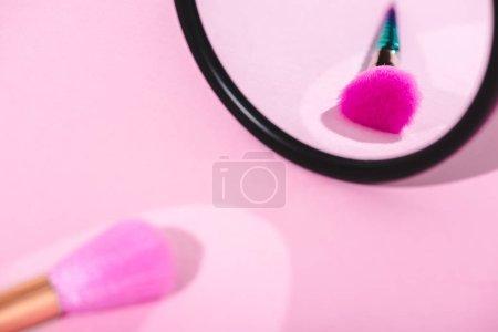 Photo pour Brosse de maquillage avec le reflet dans le miroir sur le rose - image libre de droit