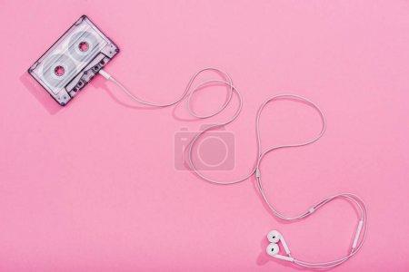 Photo pour Vue du haut de la cassette audio vintage avec écouteurs sur rose, concept musical - image libre de droit