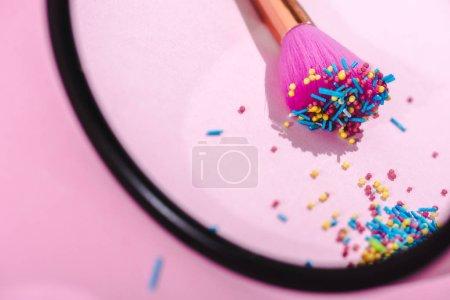 Photo pour Mise au point sélective de la brosse de maquillage couvert de saupoudrages colorés réfléchissant dans le miroir sur le rose - image libre de droit