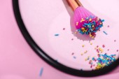 """Постер, картина, фотообои """"selective focus of makeup brush covered in colorful sprinkles reflecting in mirror on pink"""""""