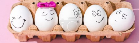 """Photo pour Plan panoramique d """"œufs avec différentes expressions du visage en carton d"""" œufs sur rose - image libre de droit"""