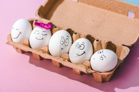Photo for Eggs with different face expressions in egg carton on pink - Royalty Free Image