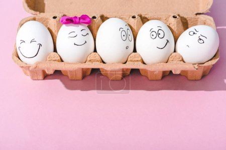 eggs with different face expressions in egg carton on pink with copy space