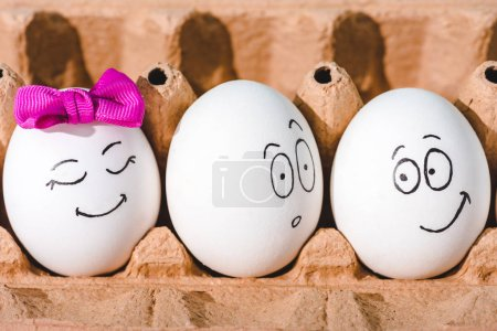 close up of eggs with smiling and shocked face expressions in egg carton