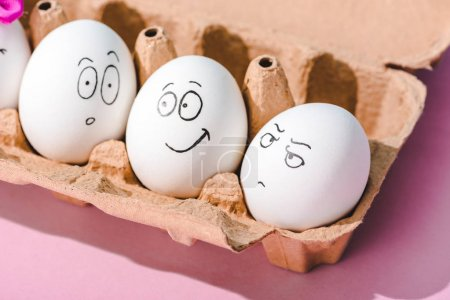 Photo for Eggs with surprised, angry and smiling face expressions in egg carton on pink - Royalty Free Image