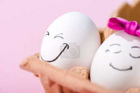 Photo for Close up of eggs with happy face expressions in egg carton Isolated On pink - Royalty Free Image