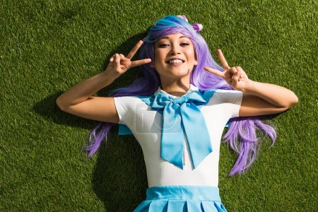 Photo pour Smiling asian anime girl lying on grass and showing peace signs - image libre de droit