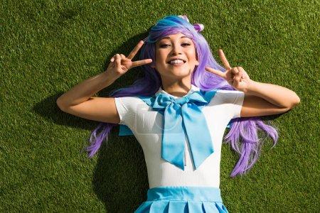Photo pour Fille asiatique de sourire d'anime se trouvant sur l'herbe et affichant des signes de paix - image libre de droit