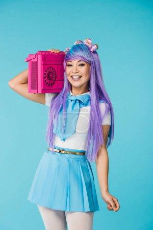 Souriant asiatique otaku fille en pourpre perruque tenant boombox isolé sur bleu