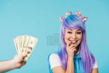 Photo pour Vue recadrée de l'homme tenant des billets en dollars et coûteux asiatique anime fille isolé sur bleu - image libre de droit