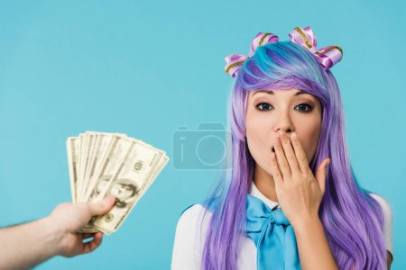 Photo for Cropped view of man holding dollar banknotes and surprised asian anime girl isolated on blue - Royalty Free Image