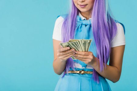 Photo for Cropped view of anime girl in purple wig counting dollar banknotes isolated on blue - Royalty Free Image