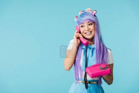 Smiling asian anime girl talking on telephone isolated on blue