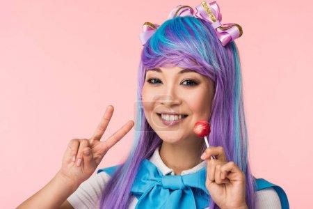 Photo pour Fille asiatique heureuse d'anime retenant la sucette et affichant le signe de paix d'isolement sur le rose - image libre de droit